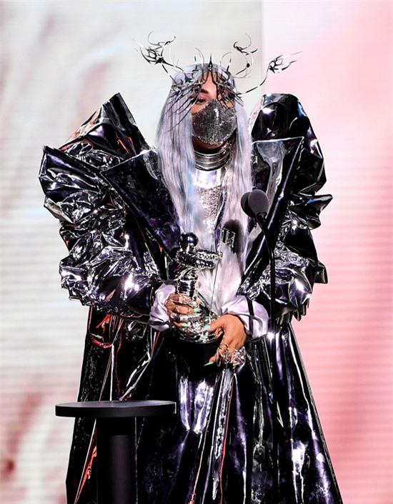 Lady Gaga được vinh danh giải thưởng MTV Tricon trên sân khấu tại Trung tâm Barclays ở Brooklyn, New York. Đây là giải thưởng mới của MTV Video Music Awards trao cho nghệ sĩ có cống hiến nổi bật trong năm với nền âm nhạc, thời trang và hoạt động xã hội.Gaga mặc bộ đầm bạc ánh đen lấp lánh, xếp li cầu kỳ, đeo khẩu trang cùng tông màu. Cô tạo thêm điểm nhấn với chiếc bờm hình cánh chim trên đầu. Gaga nhắn nhủ với khán giả: Hãy đeo khẩu trang, đó là biểu hiện của sự tôn trọng.