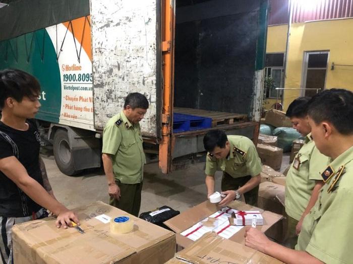Công chức Đội QLTT số 2 kiểm tra hàng hóa vận chuyển trên phương tiện chuyển phát của Viettel, ảnh: Nguyễn Thịnh.