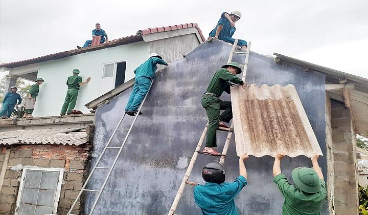 Giúp các hộ dân lợp lại nhà cửa bị bão số 5 làm tốc mái.