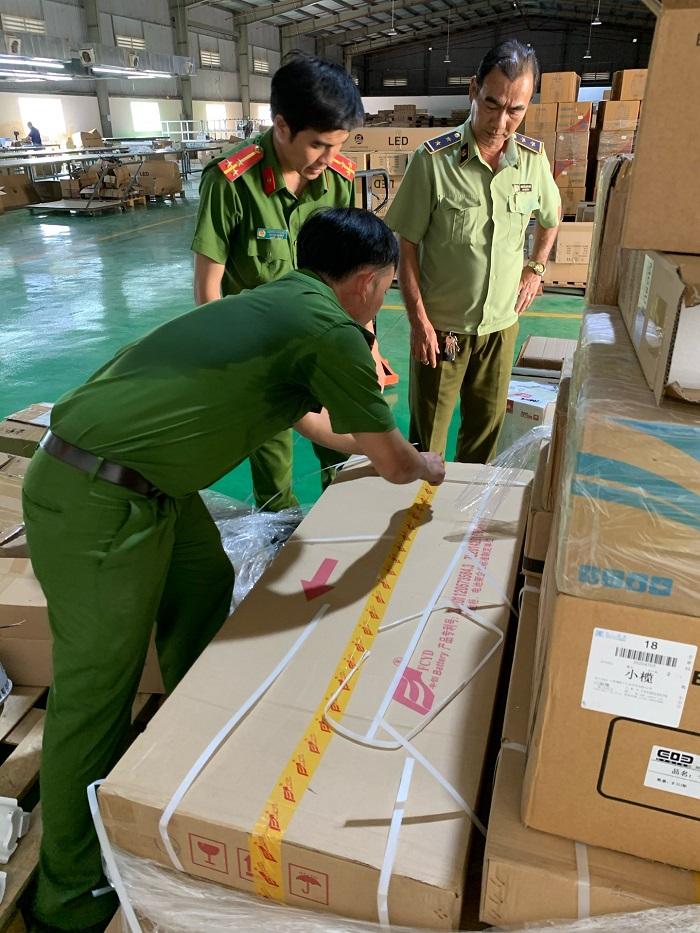 Lực lượng chức năng đang tiến hành kiểm tra và tịch thu lô hàng nghi nhập lậu tại cơ sở kinh doanh.