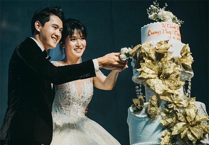Vợ chồng Thảo Trang tay trong tay cắt bánh cưới.