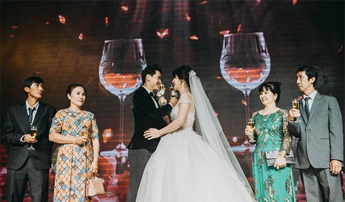 Cô dâu, chú rể vòng tay uống rượu giao bôi trong sự chứng kiến của bố mẹ hai bên và tất cả khách mời.