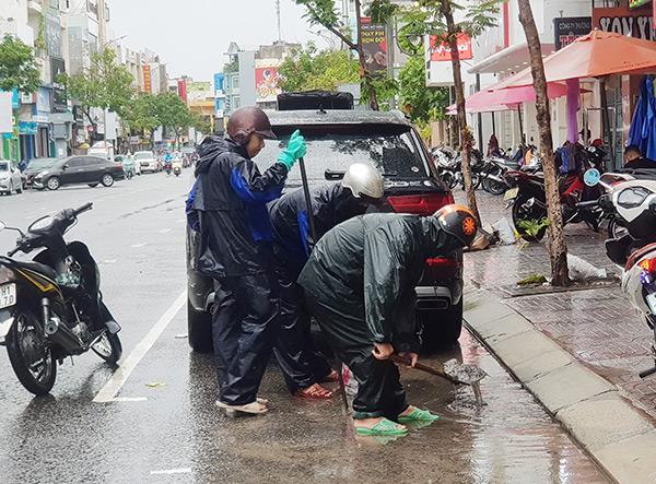 Người dân Đà Nẵng chủ động khơi thông các cửa thu nước xuống cống để giảm thiểu tình trạng ngập úng đô thị do mưa lớn kéo dài