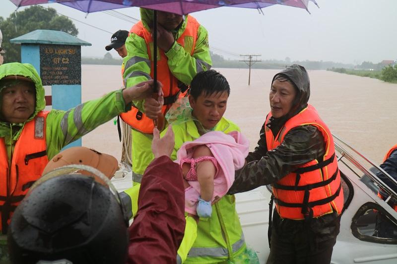 Lực lượng vũ trang đưa dân ra khỏi vùng ngập sâu.