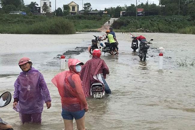 Người dân xã Tịnh An, TP Quảng Ngãi lội qua đoạn sông Trà Khúc bị nước lũ chia cắt. (Ảnh: Báo điện tử Người lao động)