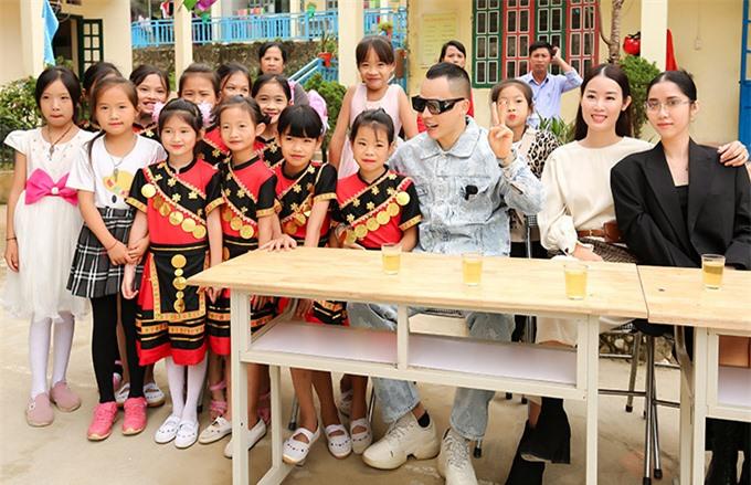 Ông bầu thân thiện chụp ảnh cùng các em nhỏ người dân tộc.