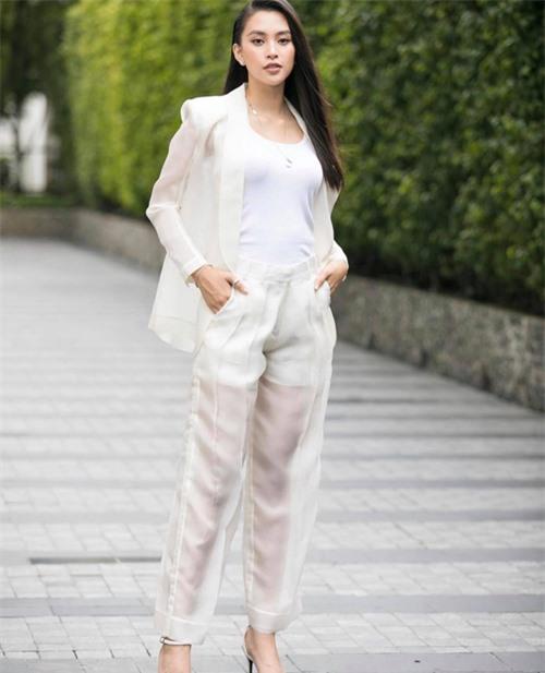 Tiểu Vy cập nhật trend diện suit trong suốt. Hoa hậu chọn áo thun trắng kiểu sát nách và dáng ôm sát hình thể để mix cùng áo blazer và quần may bằng vải organza.
