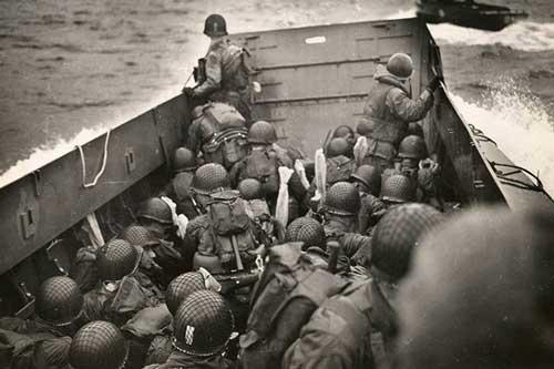 Binh sĩ lèn chật cứng bên trong chiếc tàu đổ bộ LCVP khi con tàu phi qua cơn sóng dữ. Không xa đó là bờ biển Normandy. Ảnh nguồn: Bảo tàng ĐCTGII Quốc gia.