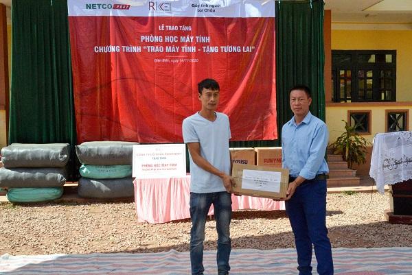 Đại diện Netco (bên trái) trao tặng phần quà gồm 250 sách tham khảo, 150 bút chì, 150 thước kẻ cho Trường phổ thông dân tộc bán trú tiểu học Nậm Nhừ.