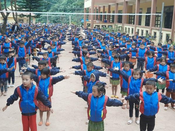 Niềm vui của các em học sinh khi được tặng những chiếc áo ấm và dép mới.
