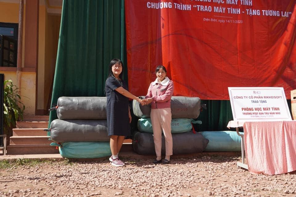 Đại diện Quỹ Tình người Lai Châu (bên trái) trao tặng quà là những chiếc áo ấm, dép, thuốc bổ cho trường tiểu học Nậm Nhừ.