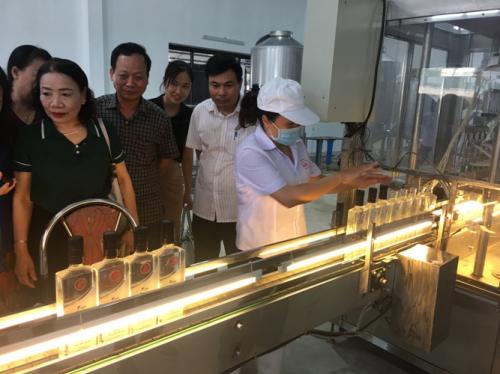Đại diện công ty Dạ Lan và khách hàng tham quan nhà máy sản xuất rượu của Công ty CP Dạ Lan.