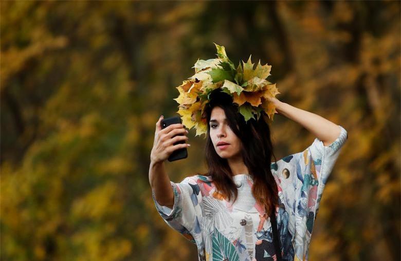 Một phụ nữ chụp ảnh với lá vàng trong công viên ở Moscow, Nga ngày 14/10.