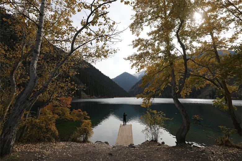 Một người đàn ông chụp ảnh trong một ngày mùa thu tại hồ Kolsai ở vùng Almaty, Kazakhstan ngày 30/9.