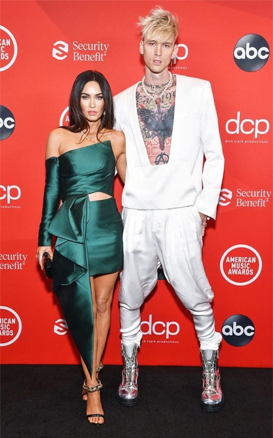 Megan Fox và Machine Gun Kelly sánh đôi trên thảm đỏ tại nhà hát Microsoft, Los Angeles. Cặp đôi ton sur ton với đồ cắt xẻ phóng túng. Megan tự tin khoe vóc dáng thanh mảnh dù đã là mẹ của ba cậu con trai.