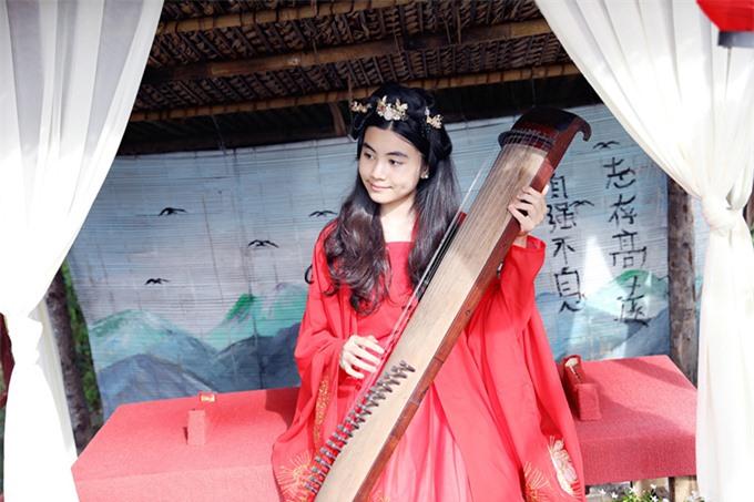 Con gái út của Quyền Linh - bé Hạt Dẻ ra dáng thiếu nữ ở tuổi 12. Nhóc tỳ thích thú khi hóa mỹ nhân thời xưa tạo dáng với cây đàn tranh.