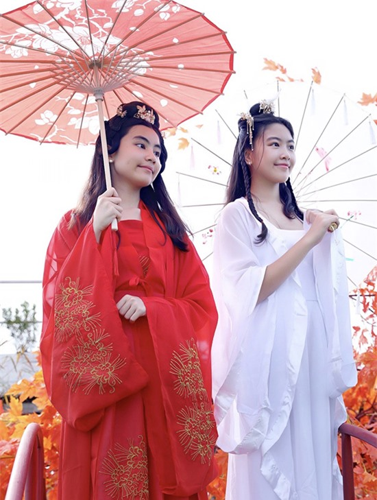 Hai chị em như Thúy Vân - Thúy Kiều e ấp che ô, đứng ngắm cảnh bên cầu.