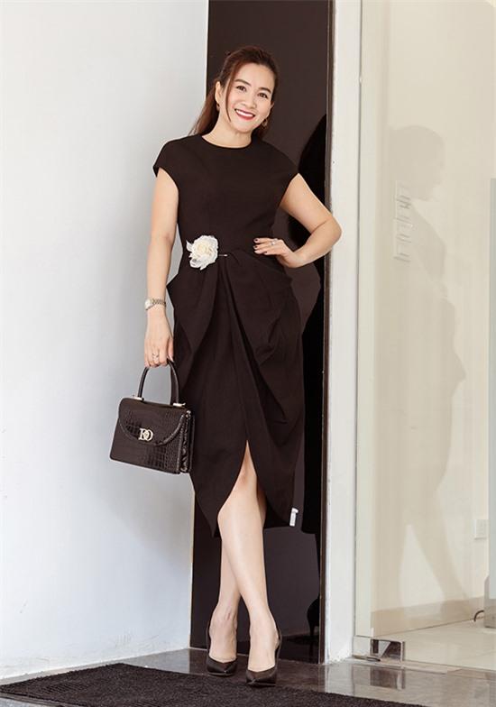 Doanh nhân Anh Thơ thanh lịch với thiết kế được tạo phom bằng những đường xếp li, gấp nếp thời thượng, mang dấu ấn đặc trưng của Đỗ Mạnh Cường. Hoa cài màu trắng tương phản làm điểm nhấn cho trang phục. Nữ doanh nhân chọn túi da màu đen phối cùng giày cao đồng màu sắc.