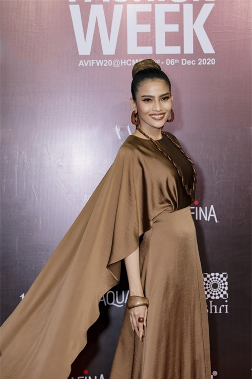 Người đẹp Trương Thị May mix-match phụ kiện gỗ đồng điệu với tông màu trầm của váy lụa.