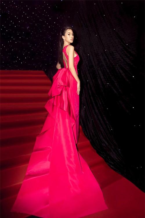 Hoa hậu Tiểu Vy nổi bật trên thảm đỏ với mẫu váy hồng cánh sen được tạo khối bắt mắt phần đuôi váy. Trang phục của Công Trí được thiết kế trên chất liệu vải lụa Italy cao cấp.