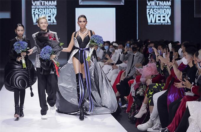 [Caption]Trang phục swimsuit tông đen được mix cùng đai lưng và tấm dù bay ánh bạc mang âm hưởng phi hành gia giúp Võ Hoàng Yến nổi bật trên sàn diễn.