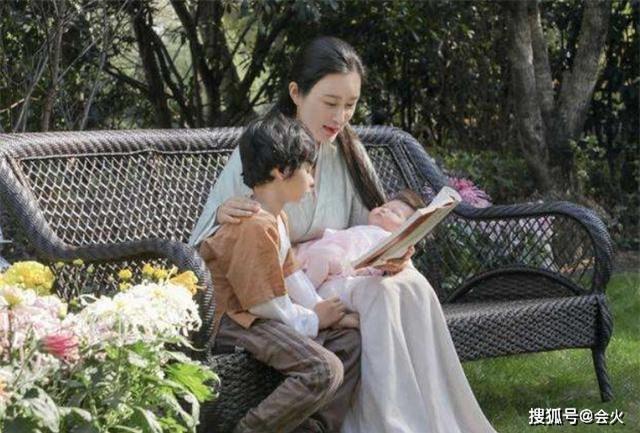 Đỗ Tinh Lâm cùng con trai riêng và con gái mới sinh ngồi trong vườn đọc sách.