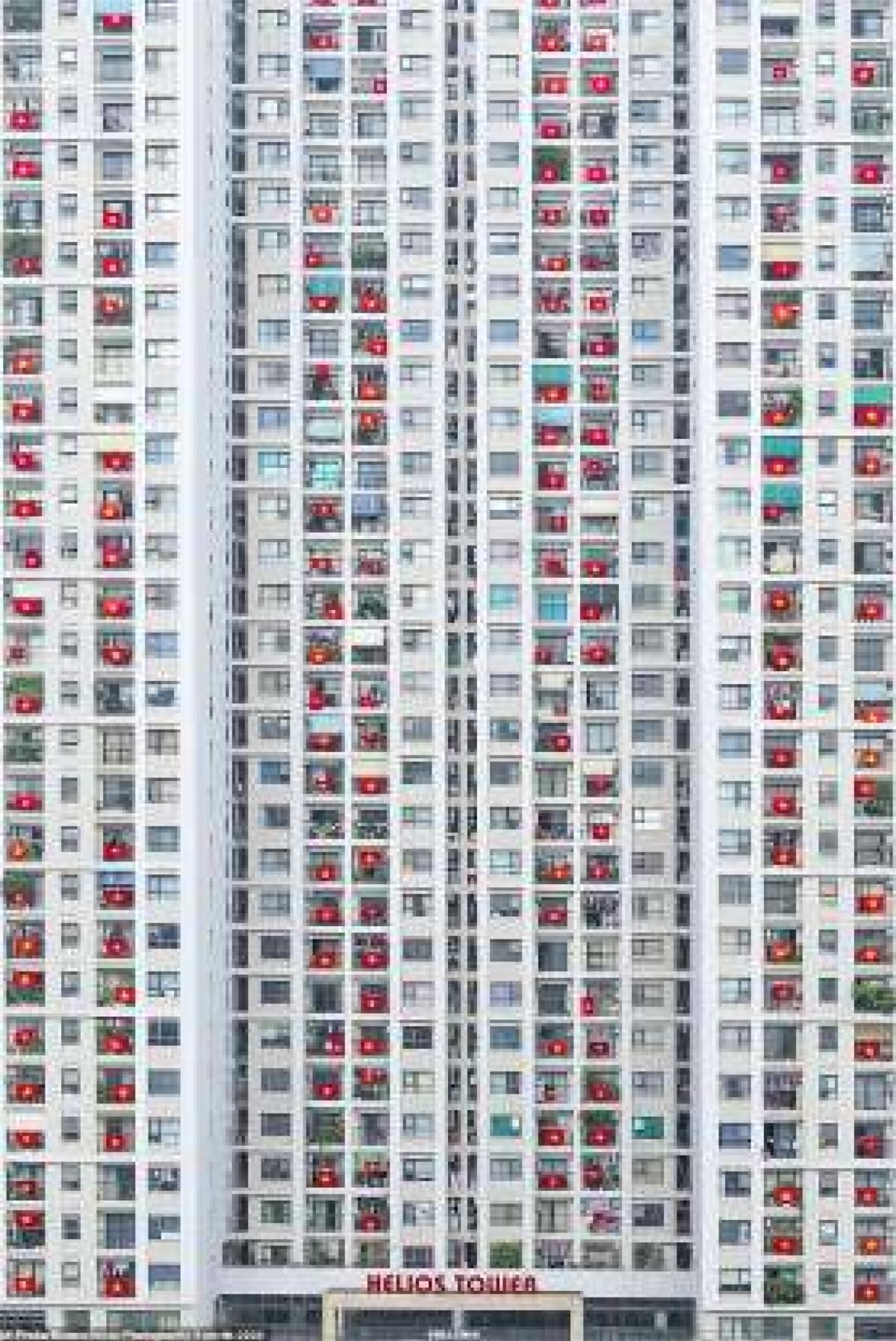 """Một trong những bức ảnh ấn tượng nhất với chủ đề Thế giới trong Lệnh phong tỏa của một người Ấn Độ tên là Prabu Mohan. Tác giả bức ảnh chia sẻ: """"Đây là tòa nhà gần nhà của tôi ở Việt Nam. Người dân của các tòa nhà này đã treo quốc kỳ Việt Nam để thể hiện sự khích lệ với những người chiến đấu chống dịch Covid-19 nơi tuyến đầu""""."""