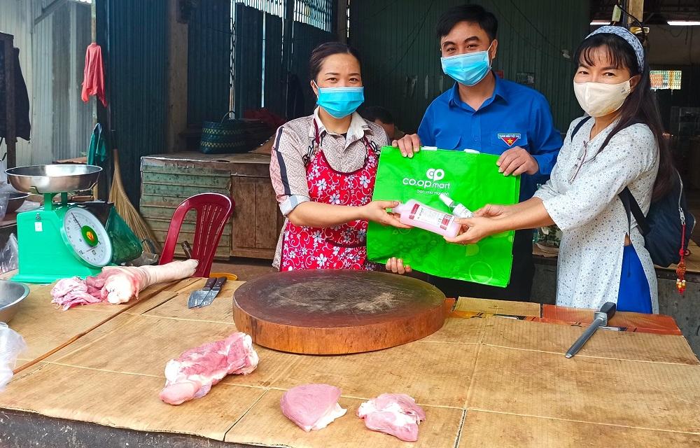 Bí thư Tỉnh Đoàn Bình Phước Trần Quốc Duy (giữa) và nhà báo Minh Thùy (bìa phải) trao nước rửa tay sát khuẩn và túi nhựa sử dụng nhiều lần cho một hộ bán thịt heo tại khu vực chợ thuộc xã Tân Hưng.