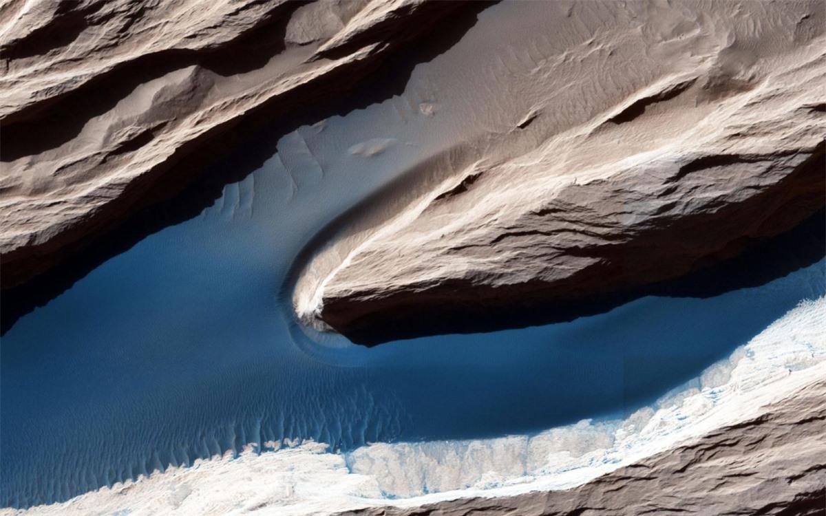 Mặc dù sao Hỏa không hoạt động địa lý giống như Trái Đất nhưng các đặc điểm trên bề mặt hành tinh này chủ yếu được định hình bởi gió. Những địa hình được điêu khắc như thế này, được gọi là yardang, vốn rất phổ biến trên hành tinh đỏ. Trên cát, gió sẽ tạo thành những gợn sóng lăn tăn và những đụn cát nhỏ. Do bầu khí quyển trên sao Hỏa rất mỏng nên ánh sáng không phân tán được nhiều, vì thế, bóng của các yarrdang rất tối và sắc nét.