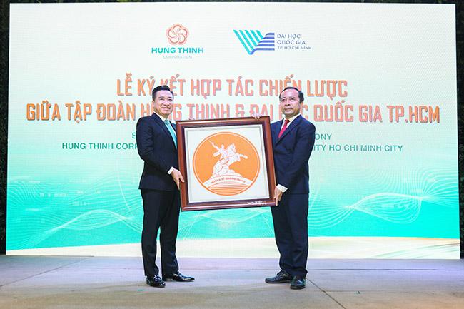 Ông Nguyễn Đình Trung, Chủ tịch Tập đoàn Hưng Thịnh trao quà lưu niệm cho PGS.TS Vũ Hải Quân, Ủy viên Trung ương Đảng, Giám đốc Đại học Quốc gia TPHCM.