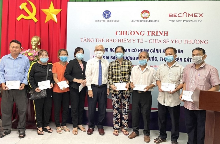 Ông Phạm Ngọc Thuận, Tổng Giám đốc Becamex IDC trao tặng thẻ Bảo hiểm y tế cho người dân.