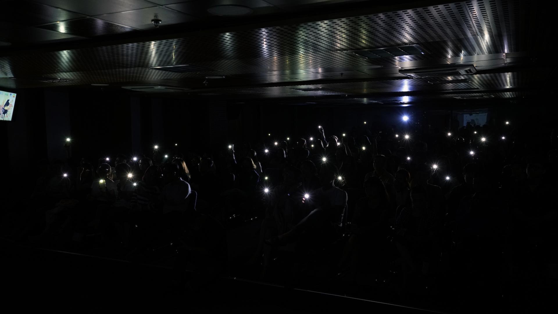 """Hàng trăm bạn trẻ cùng bật đèn flash trên điện thoại thông minh để hòa mình vào, cổ vũ cho phần trình bày của nhóm AMER với bài hát """"Thế giới không phiền lo"""""""