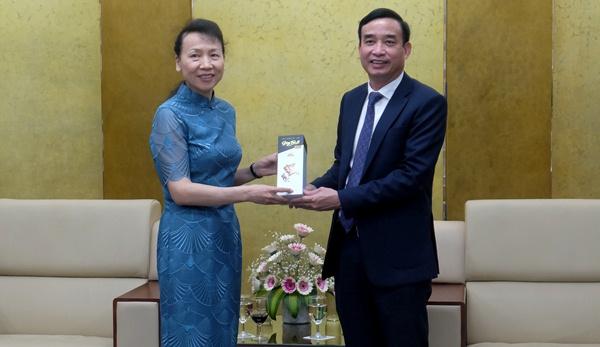 Chủ tịch UBND thành phố Lê Trung Chinh trao quà lưu niệm cho bà Đổng Bích Du