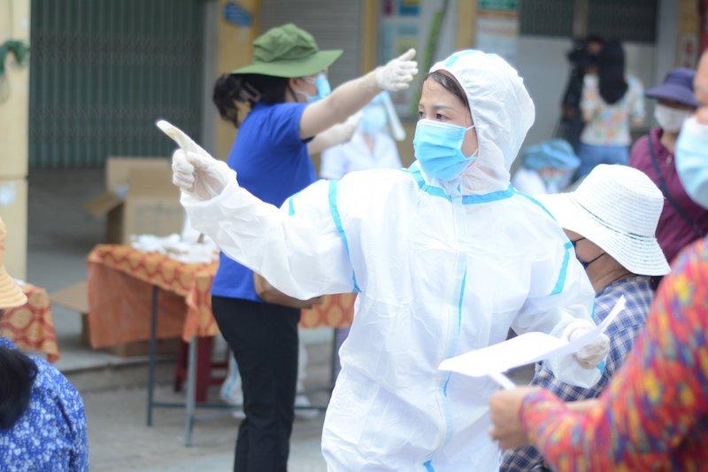 Lực lượng y tế hỗ trợ các tiểu thương trước khi lấy mẫu