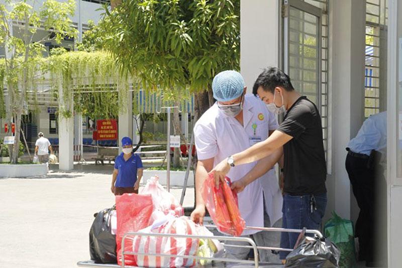 Nhân viên Bệnh viện C Đà Nẵng kiểm tra các nhu yếu phẩm gửi cho bệnh nhân. (Ảnh: Văn Dũng/TTXVN)