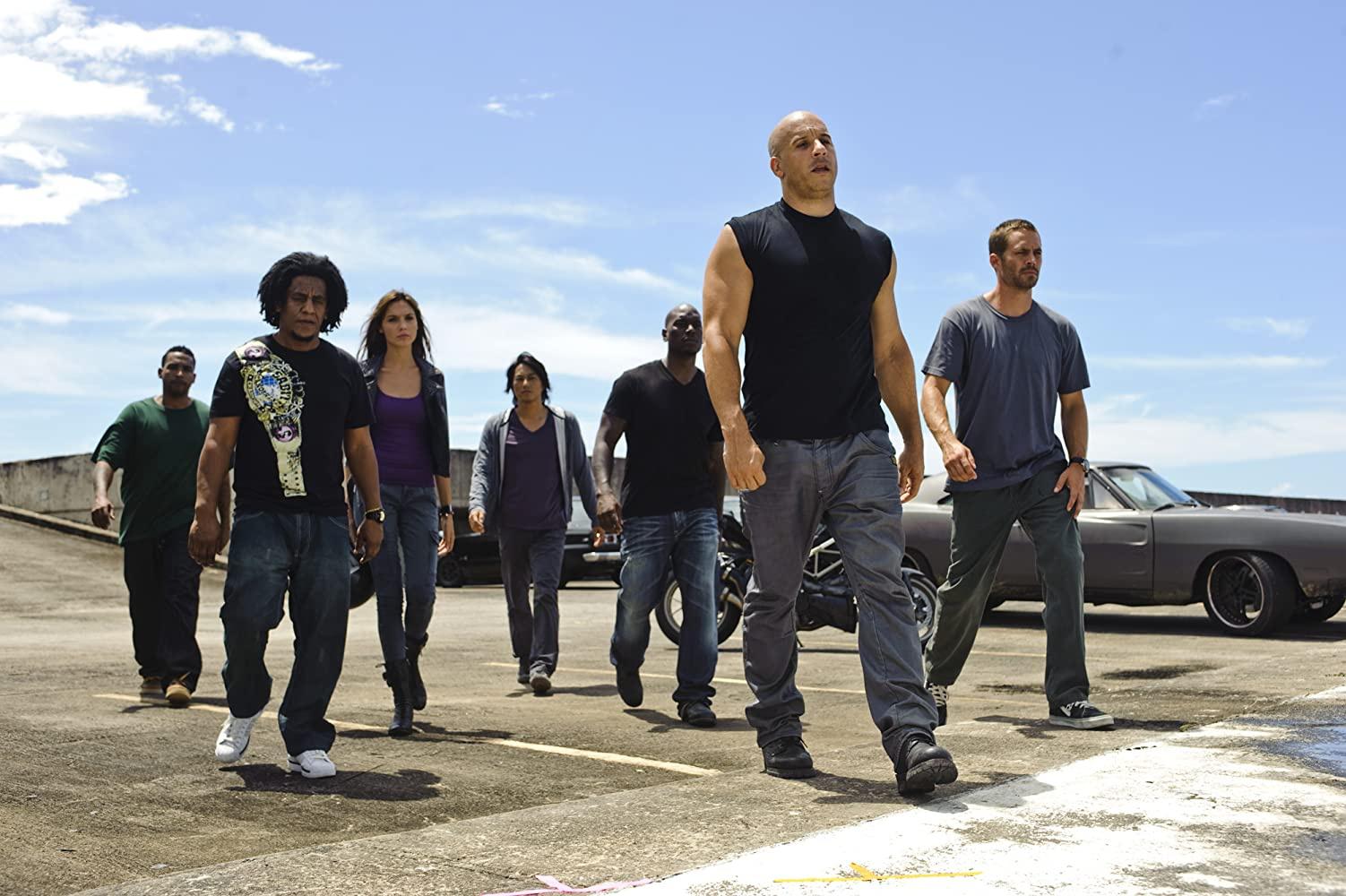 """Vụ cướp xe tù trong Fast Five (2011): Bộ phim mở ra bằng cảnh Dom đang bị chuyển đi bằng xe tù, còn """"gia đình"""" của anh thì chuẩn bị thực hiện vụ cướp tù. Mia (Jordana Brewster), em gái của Dom, chặn chiếc xe tù bằng cách vượt lên và đột ngột bẻ lái, khiến chiếc xe phải chuyển hướng. Trong khi đó, Brian (Paul Walker) đón lõng và đạp phanh, khiến chiếc xe tù văng khỏi đường cao tốc."""