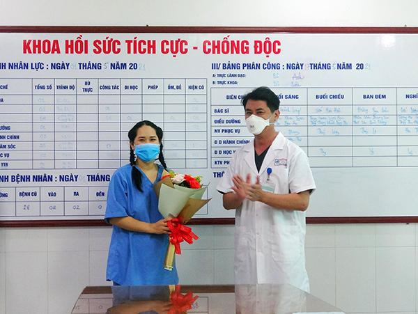 TS.BS Lê Đức Nhân, Giám đốc Bệnh viện Đà Nẵng tặng hoa chúc mừng nữ điều dưỡng sốc phản vệ sau khi tiêm vaccine Covid-19 được xuất viện ngày 17/5