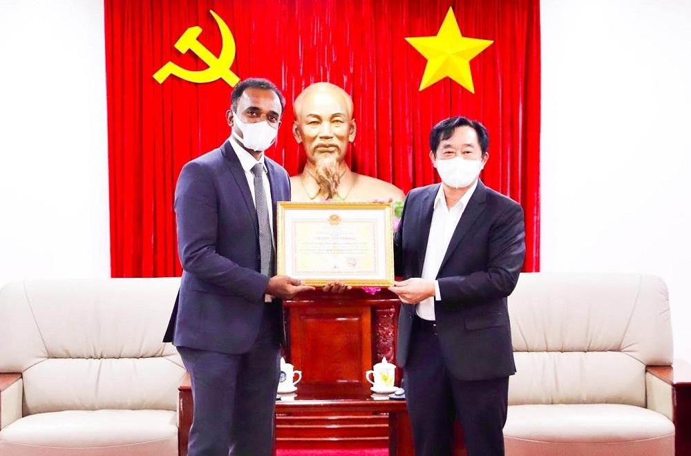"""Chủ tịch UBND tỉnh Bình Dương Nguyễn Hoàng Thao tặng hoa tri ân và trao chứng nhận """"Tấm lòng vàng nhân đạo"""" cho Công ty P&G Việt Nam."""