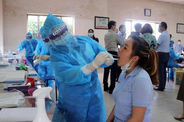 Nhân viên y tế lấy mẫu xét nghiệm cho công nhân làm việc tại các khu công nghiệp. (Ảnh: TTXVN phát)