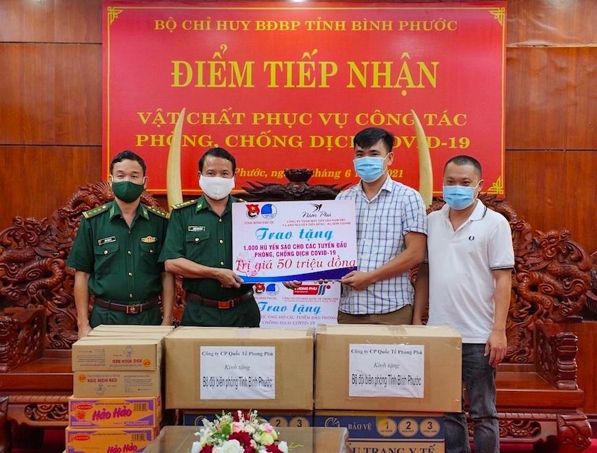 Anh Trần Tuấn Anh (Giám đốc công ty TNHH MTV Yến Sào Nam Phú (thứ hai, phải sang) và anh Nguyễn Tiến Dũng (bìa phải) trao 1.000 hũ yến sào cho đại diện BCH Bộ đội biên phòng tỉnh Bình Phước