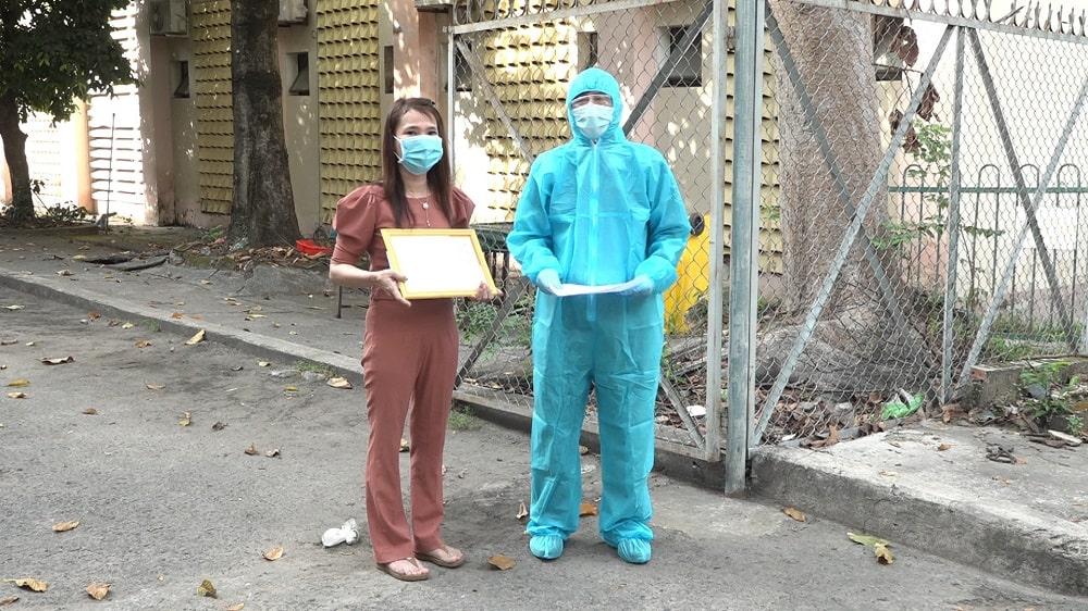 Ông Nguyễn Văn Tuấn - Giám đốc Trung tâm Y tế huyện Châu Thành trao tặng giấy khen và tiền thưởng cho chị X. trong lúc cách ly.