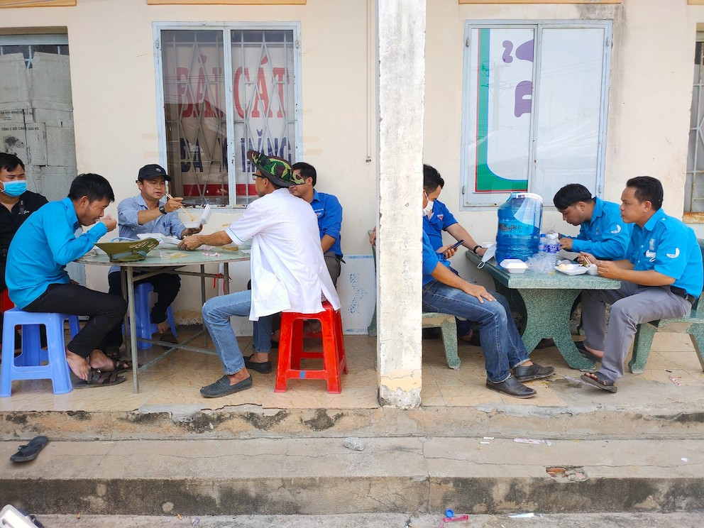 Bữa cơm vội vã tại chốt phòng dịch trên đường ĐT 741 (đoạn thuộc xã Tân Lập, huyện Đồng Phú, Bình Phước) trong cuộc chiến chống Covid-19 của những chiến sĩ áo xanh tình nguyện dưới cái nắng oi bức của mùa hè đỏ lửa