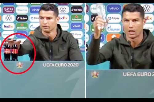 Ronaldo bỏ 2 chai Coca-Cola ra khỏi bàn họp báo.