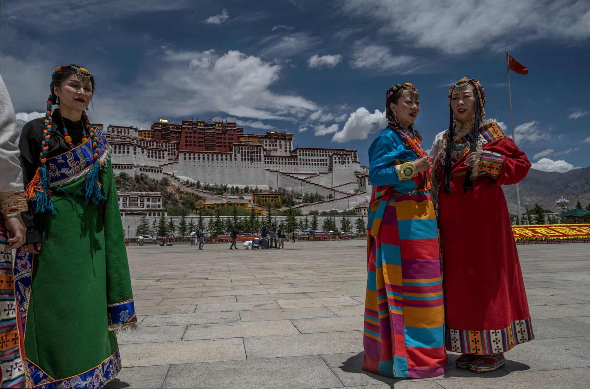 Các cô gái trong bộ trang phục truyền thống đứng trước điện Potala. Chuba, loại áo khoác làm từ da cừu, khá phổ biến với những người du mục.