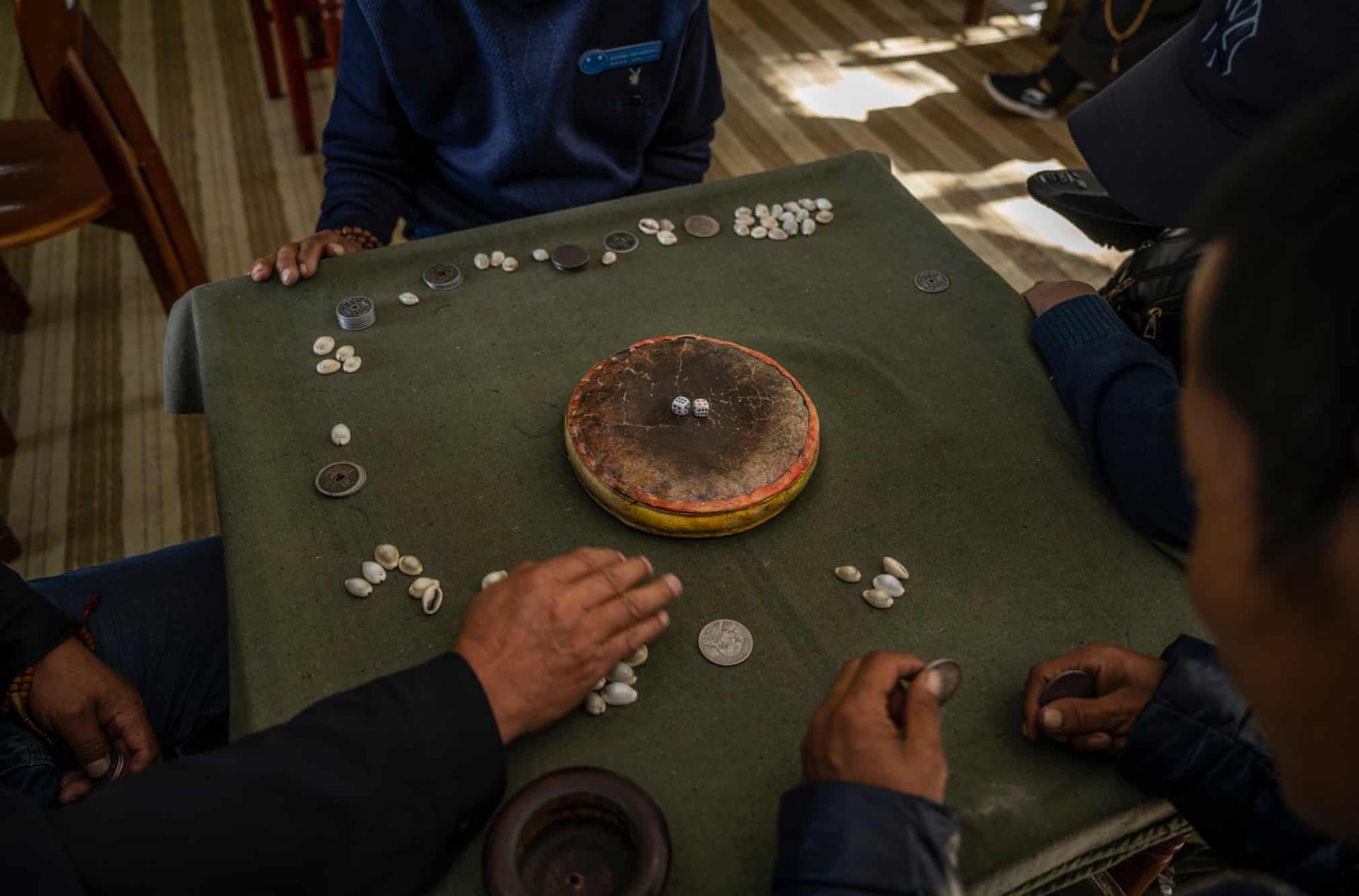 """Những người này đang chơi một trò chơi truyền thống của Tây Tạng tại viện dưỡng lão Caigongtang. Trò này có tên là """"sho"""" và thường được những người đàn ông chơi cược tiền."""