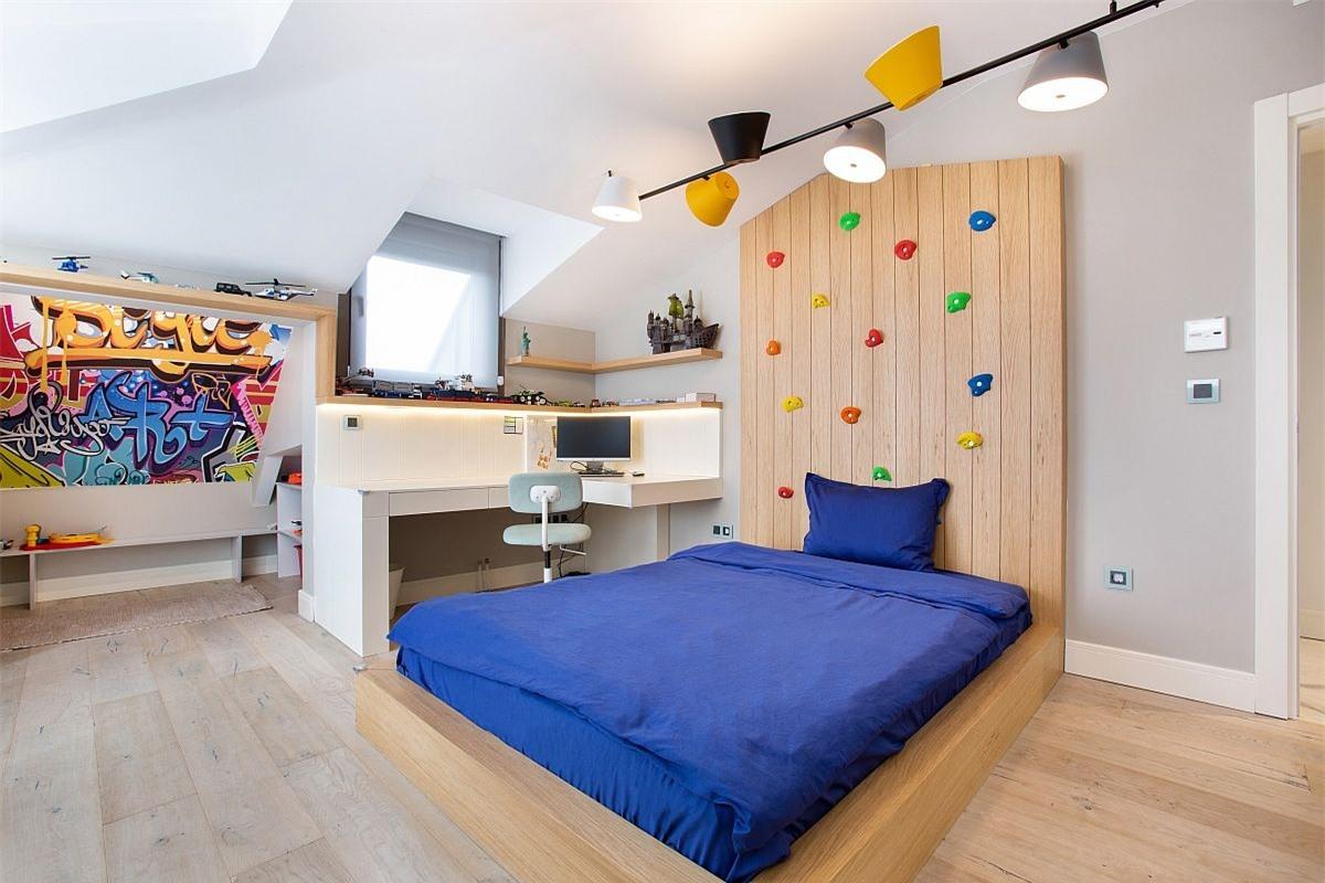 Phòng ngủ dành cho bọn trẻ vô cùng hiện đại với những gam màu trung tính kết hợp cùng khu học tập nhỏ gọn, bức tường leo núi.