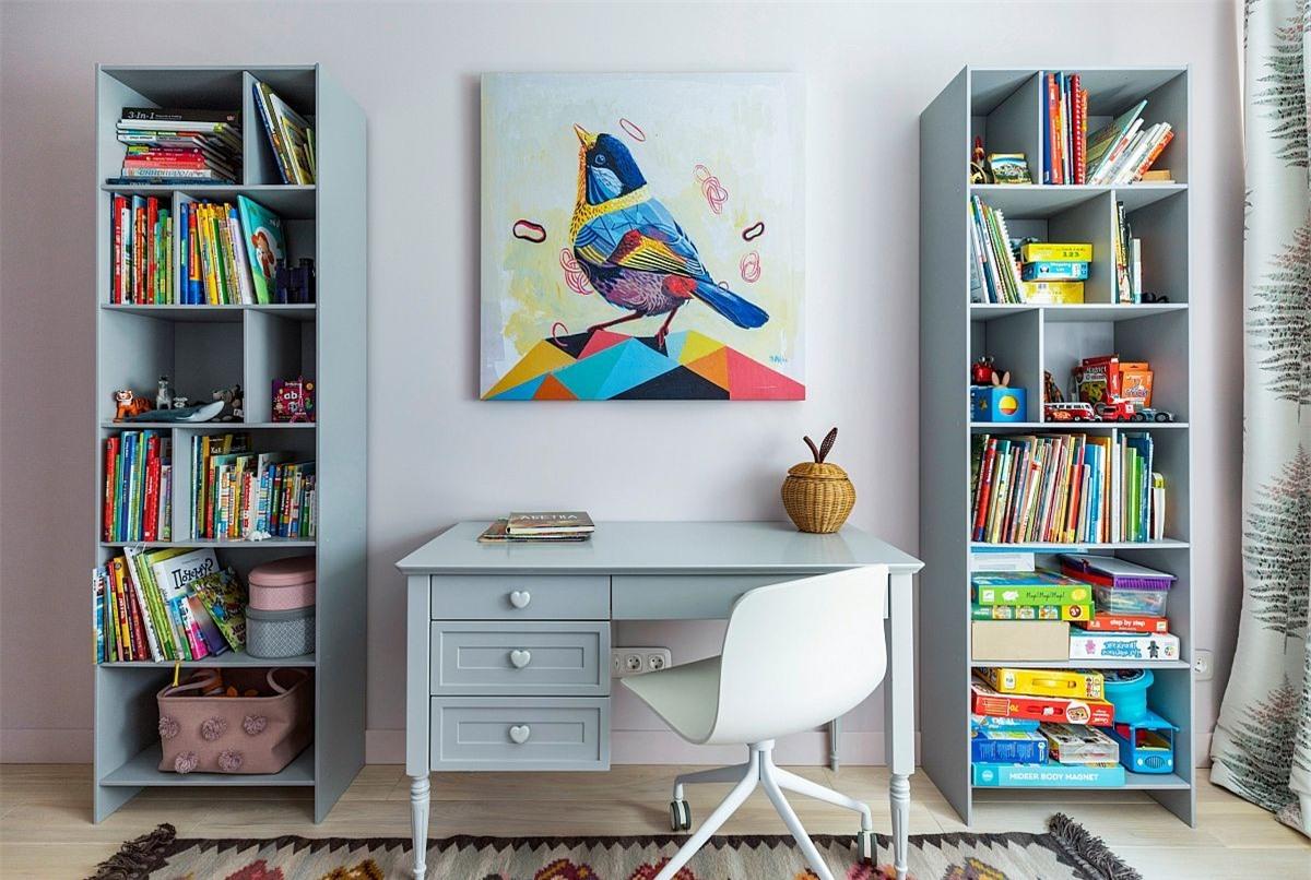 Bức tranh đa màu sắc cùng kệ lưu trữ lớn được bố trí xung quanh bàn học tập nhỏ đã tạo nên một không gian thư giãn và tuyệt đẹp.