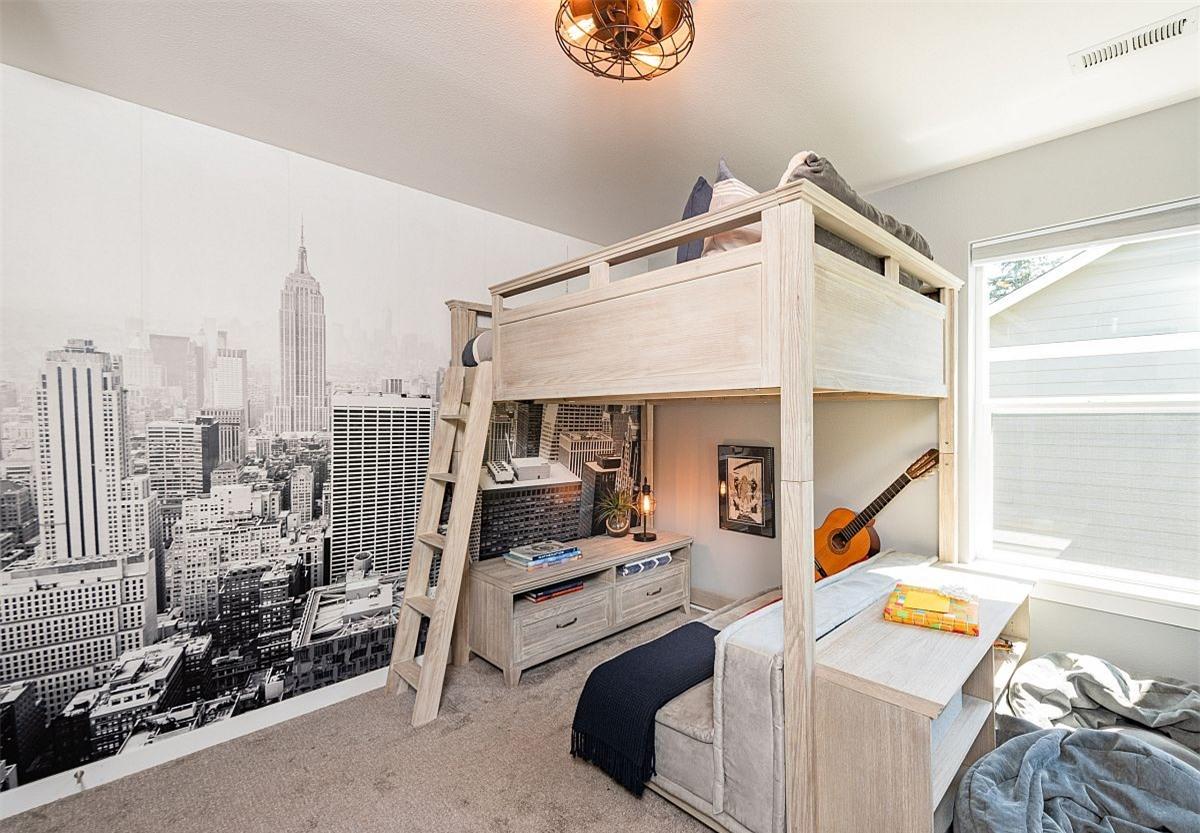 Phòng ngủ dành cho bé trai khá sinh động với bức tranh quang cảnh thành phố cùng chiếc giường gác xép có góc học tập bên dưới.