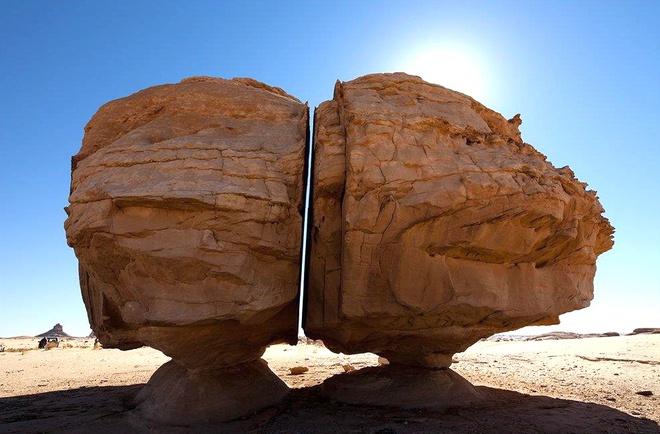 Tảng đá Al Naslaa nằm ở ốc đảo sa mạc Tayma, Arab Saudi, Tây Á. Khối đá nặng hàng trăm tấn đứng cân bằng trên một phiến đá mỏng. Năm 1883, Charles Huver phát hiện tảng đá này bị tách thành 2 nửa bằng nhau bởi vết nứt thẳng và nhẵn đến khó tin, mỗi phần cao khoảng 7 m. Nguồn gốc vết cắt đến nay vẫn chưa có lời giải thích thỏa đáng. Ảnh: Destinationksa.