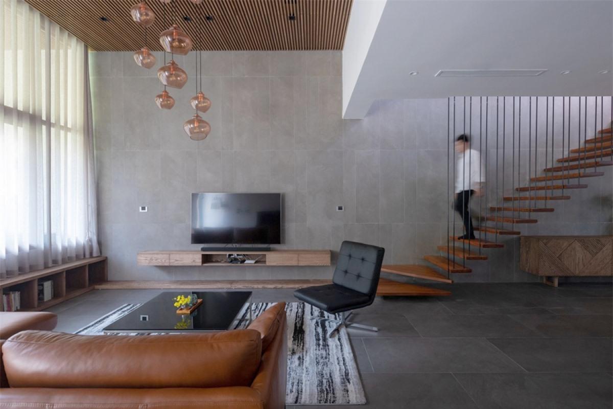 Ở tầng 1 là không gian liên thông phòng khách – bếp và phòng ăn. Cầu thang lên tầng trên được thiết kế nép vào một bên để tạo không gian rộng mở.